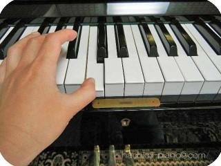 アップライトピアノの真ん中のドを左手で弾く。